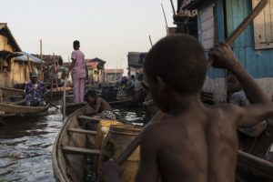 On 20 October 2016 in Lagos, Nigeria, a child navigates the polluted waters of Makoko, a fishing community mostly made up of structures on stilts above Lagos Lagoon. Vehicle emissions, diesel generators, burning of biomass and garbage and other environmental waste greatly affect the communities water and air quality. Residents of Makoko rely on fishing to make a living and complain that the fish stock has dwindled in recent years as a result. They also have trouble breathing and many cough out soot on a daily basis. Almost one in seven of the worldís children, 300 million, live in areas with toxic levels of outdoor air pollution - six times higher than international guidelines according to a report from UNICEF, Clear the Air for Children, released ahead of COP 22. UNICEFís findings, the first of its kind and based on satellite imagery, also show that around 2 billion children in total live in areas where outdoor air pollution exceeds limits set by the World Health Organization as being safe for human health. This air pollution is caused by factors such as vehicle and factory emissions, heavy use of fossil fuels, dust and burning of waste. Indoor pollution is commonly caused by use of fuels like coal and wood for cooking and heating. Taken together, outdoor and indoor air pollution are one of the leading dangers facing children -- they are a contributing factor in the deaths of almost 600,000 children under five every year. This figure represents nearly 1 in 10 under-five deaths. Air pollution is also linked with poor health and diseases among millions more children that can severely affect their overall wellbeing and development. It causes difficulty breathing; studies show it is linked with, and can exacerbate asthma, bronchitis, and the inflammation of airways, as well as other underlying health issues. Children who breathe polluted air are at higher risk of potentially severe health problems-- in particular, acute respiratory infections such as pneumoni